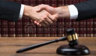 51090429-martelletto-sul-tavolo-in-legno-con-il-giudice-e-il-cliente-si-stringono-la-mano-in-background-in-au